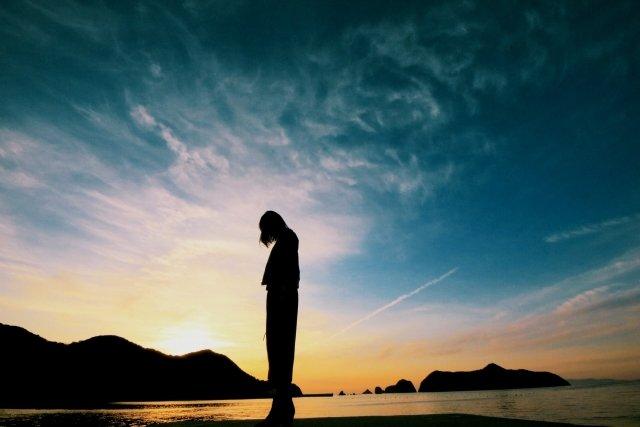 海岸でうなだれる女性のシルエット